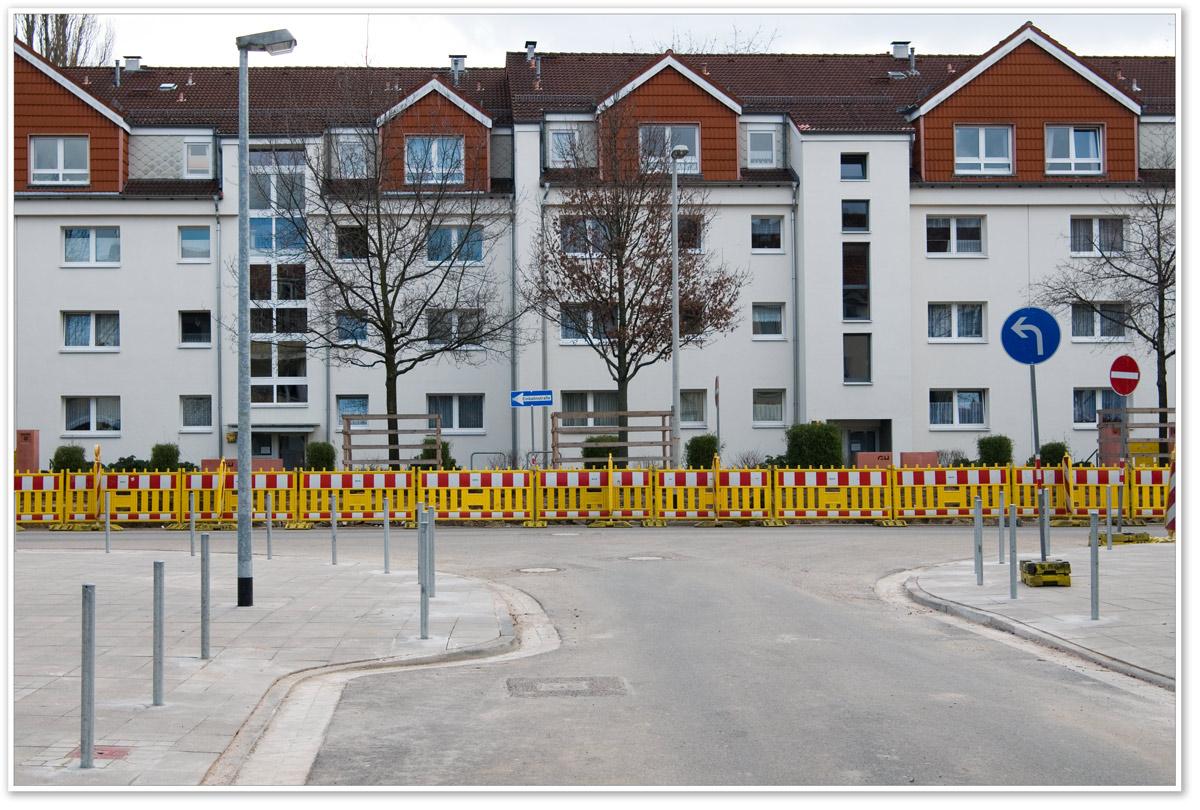 Schrankenzaun einer Baustelle vor Häuserzeile